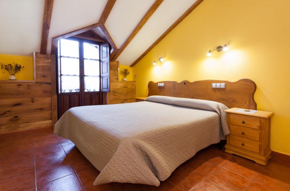 Habitacion abuardillada con cama de matrimonio.