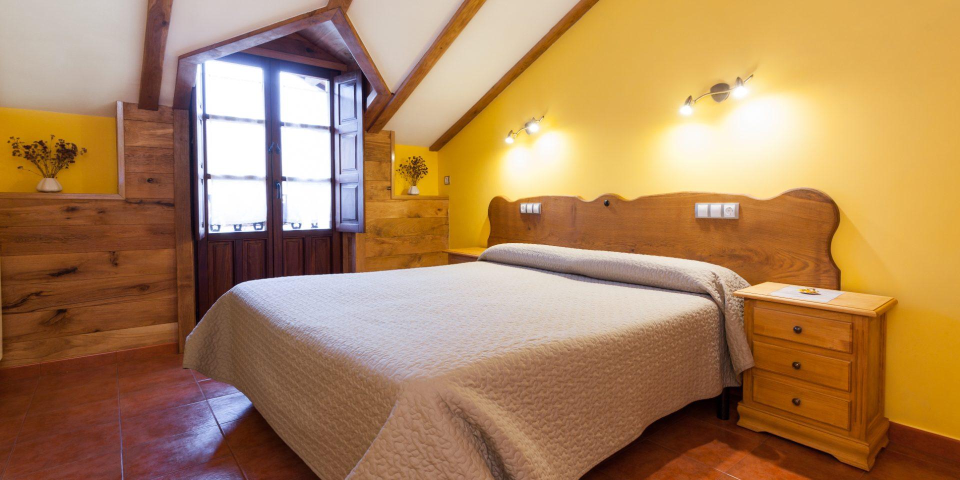 Habitación abuardillada con cama de matrimonio.